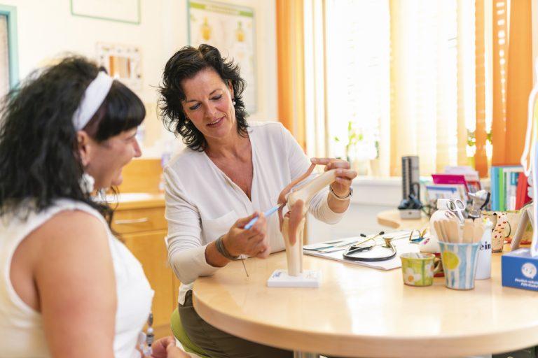 Doktor Peggy Lampel erklärt einer Patientin anhand eines Kniegelenkes wo das Problem liegt